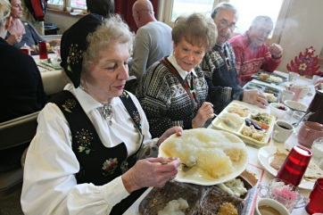 Janet Lunde-Landwehr of Hartland, takes a helping of lutefisk. She is wearing a bunad, a ceremonial dress worn in Norway to social functions. Her friends at right, Marion Sorenson of Oconomowoc, and husband Bob Sorenson and Chet Seffrood of Oconomowoc, look on with anticipation.